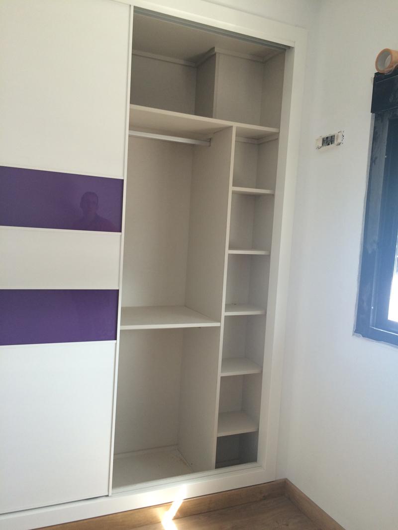 Armario empotrado con puertas correderas e interior con perchero y estanterias